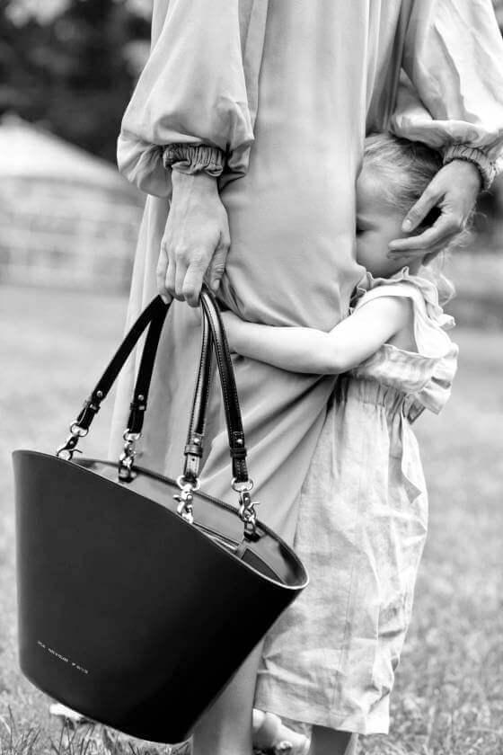 złam zasady wybierz czerń kobieta przytulająca dziecko z torebką Chylak
