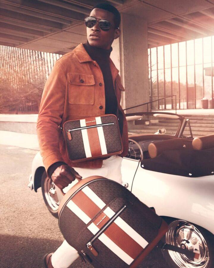 model w kurtce i z  torebkami od Michael Kors