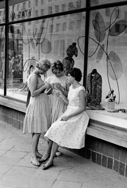 kobiety plotkujące ze sobą pod sklepem