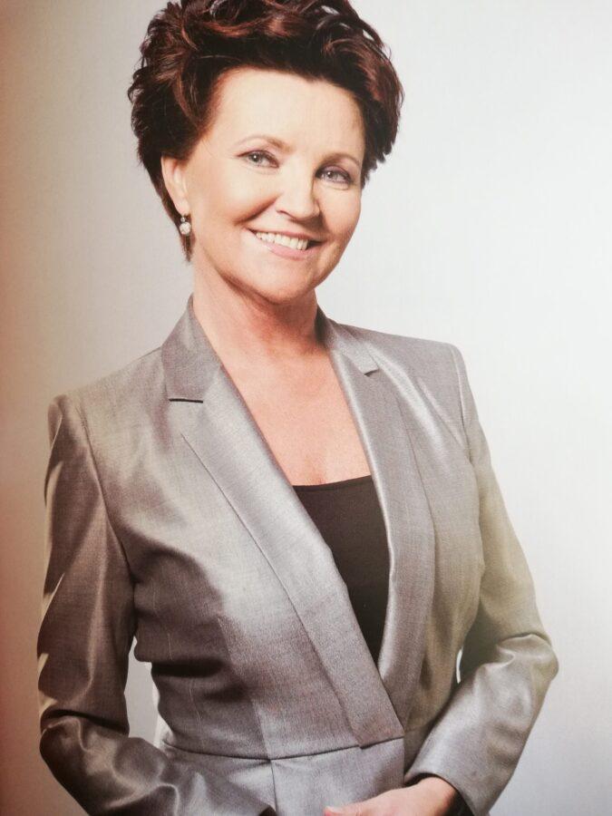 Jolanta Kwaśniewska w szarym garniturze