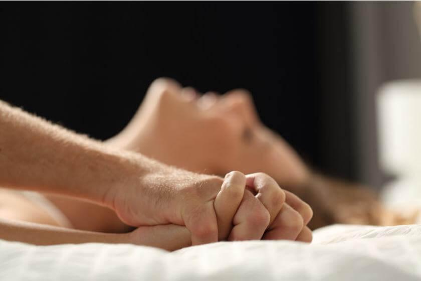 seks w łóżku i złączone dłonie